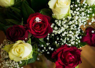 un bouquet de roses rouges et blanches avec une bague